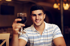 Handsome Man Raising Wine Glass in Toast. Portrait of a young guy celebrating with red wine Stock Photo