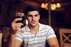 Handsome Man Raising Wine Glass in Toast. Portrait of a young guy celebrating with red wine Stock Photos