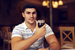Handsome Man Raising Wine Glass in Toast. Portrait of a young guy celebrating with red wine Royalty Free Stock Photo