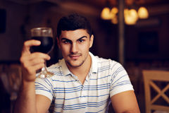 Handsome Man Raising Wine Glass in Toast. Portrait of a young guy celebrating with red wine Stock Images