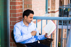 Handsome man reading on balcony Stock Image