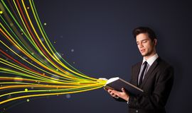 Handsome man reading a book while colorful lines are coming out of the book stock image