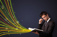 Handsome man reading a book while colorful lines are coming out Stock Photo