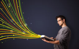 Handsome man reading a book while colorful lines are coming out Stock Images