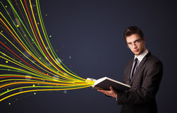 Handsome man reading a book while colorful lines are coming out Royalty Free Stock Photos