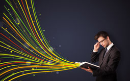Handsome man reading a book while colorful lines are coming out Stock Image