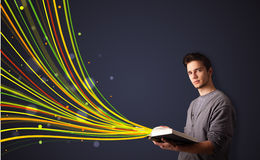 Handsome man reading a book while colorful lines are coming out Royalty Free Stock Image