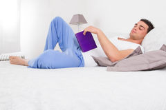 Handsome man reading book in his bed. Handsome man in pajamas reading book relaxing in his bed Royalty Free Stock Photos