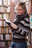 Handsome man reading book in library Royalty Free Stock Photography