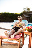 Handsome man reading book, lying on chaise near swimming pool. Young handsome man in sunglasses reading book, lying on chaise near swimming pool. Copy space stock photos