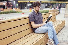 Handsome man reading book sitting outside in public space. Wearing glasses alone working. Concept of education students.  stock photo