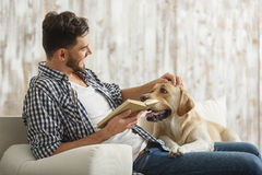 Handsome man reading book to his pet at home stock photography