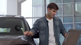 Handsome man reading info paper at car dealership, choosing new auto. Cheerful young male customer buying automobile at car salon. Consumerism, safety concept stock video
