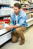 Handsome man reading the ingredients on a milk bottle Royalty Free Stock Photo