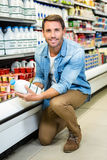 Handsome man reading the ingredients on a milk bottle Royalty Free Stock Photos