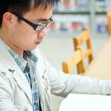 Handsome man reading in the library Stock Photo