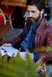A handsome man reading a magazine about art and culture. Portrait of handsome mature man with beard holding magazine in the hands looking away, attractive man stock images