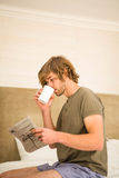 Handsome man reading the news and drinking coffee Royalty Free Stock Photo