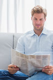 Handsome man reading a newspaper on a couch Royalty Free Stock Photo