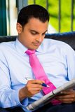Handsome man reading newspaper doing work Royalty Free Stock Image