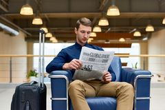 Handsome Man Reading Newspaper in Hotel Lobby stock image