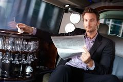 Handsome man reading newspaper in limousine. Handsome young man sitting in limousine, reading newspaper Stock Images