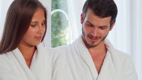 Handsome man reading poetry to his girlfriend. Gorgeous woman smiling while her husband reading her a book at home. Couple wearing bathrobes at home while stock video footage