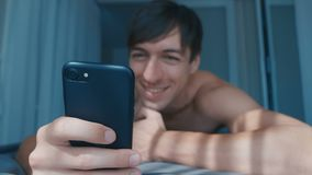 Handsome smiling man reading messages on smartphone at home lying on the bed. A young male uses a mobile phone in the stock video