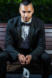 Handsome man ready to attend a masquerade party. Man sitting on a park bench wearing a tuxedo and holding a mask in his hand ready to attend a ball mask Royalty Free Stock Photos