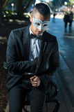 Handsome man ready to attend a masquerade party. Man sitting on a park bench wearing a tuxedo and  wearing  a mask in his hand ready to attend a ball mask.  He Royalty Free Stock Photography