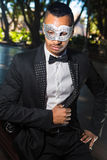 Handsome man ready to attend a masquerade party. Man sitting on a park bench wearing a tuxedo and  wearing  a mask in his hand ready to attend a ball mask Stock Photography