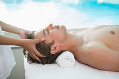 Handsome man receiving head massage at spa center Stock Photo
