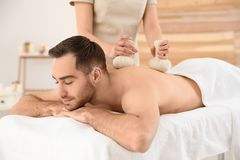 Handsome man receiving herbal bag massage. In spa salon stock photography