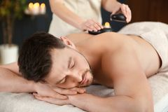 Handsome man receiving hot stone massage royalty free stock photography