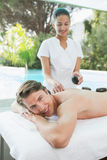Handsome man receiving stone massage at spa center Stock Photography