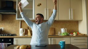 Handsome man recieve good news reading letter in the kitchen while have breakfast at home early morning Royalty Free Stock Images