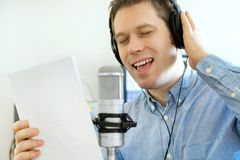 Handsome man recording a song. Handsome man recording a song in record studio Stock Photography