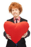 Handsome man with red heart-shaped pillow Royalty Free Stock Photography