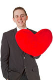 Handsome man with red heart shaped pillow Stock Photos