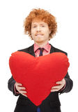 Handsome man with red heart-shaped pillow Stock Photo