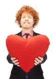 Handsome man with red heart-shaped pillow Royalty Free Stock Photos