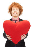 Handsome man with red heart-shaped pillow Stock Image