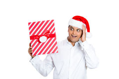 Handsome man in red santa claus hat looking surprised hands on cheek Stock Image
