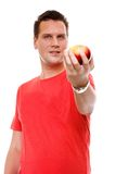 Handsome man in red shirt with apple isolated Stock Image