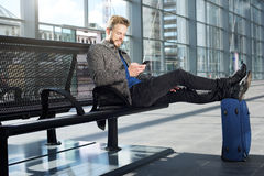 Handsome man relaxing at airport with mobile phone. Portrait of a handsome man relaxing at airport with mobile phone Royalty Free Stock Photography