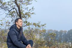 Handsome man relaxing in the autumn park Royalty Free Stock Photography