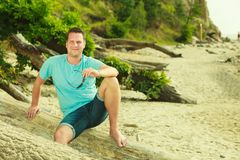 Handsome man relaxing on beach during summer. Royalty Free Stock Photos