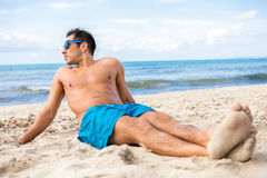 Handsome man relaxing on the beach Stock Image