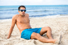 Handsome man relaxing on the beach. Handsome man wearing trendy sunglasses and his swimsuit relaxing on the beach sitting on the golden beach sand soaking up the Royalty Free Stock Photos