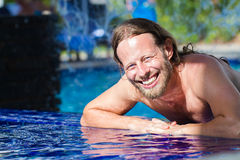 Handsome man relaxing in a blue swimming pool. Portrait of a handsome, happy man relaxing in a blue swimming pool at a tropical resort royalty free stock image